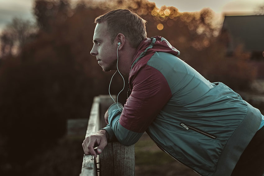 Attractive young athletic man standing on the beach and looks into the distance of the river to the bridge, listening to music